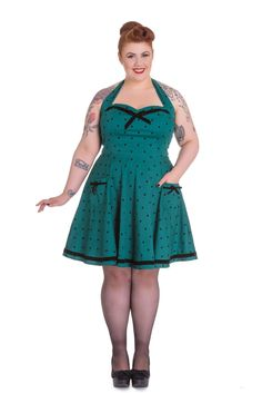 This lovely little mini dress features a curvy sweetheart neckline and black velvet trim with matching bows, a polka dot print on teal green, Lovely flattering fit, and the dress has classic thick straps. Superbly made from cotton and elastane, the dress is easy to wear casually or dress up with heels for an alternative evening look. - Imported - Material :Fabric content: 98% Cotton, 25% Elastane. - Print of black polka dots on teal green background - Halter neck Tie on back - Length: Above…