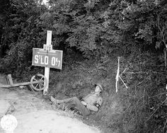 American MP rests on the roadside next to road sign pointing to Saint-Lô, Lower Normandy, France, 1944.