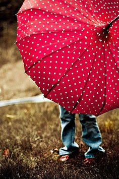 Red umbrella with white polka dots on it.