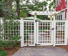 """Garden Arbor + Custom Gate Walpole Woodworkers. The elegant Arbor + fence shown here was featured on """"This Old House"""" 2013 program. It was chosen to accompany a custom walk gate with similarly styled lattice fence sections. Note the whimsical choice in horizontal/vertical spacing that gives this structure a distinctive look. Arbor, gate, and fence are handcrafted in low maintenance cellular PVC (what? PVC?!)"""