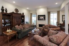Spacious living room with gleaming hardwood floors, recessed lighting, fireplace with tile surround and is open to the dining room.
