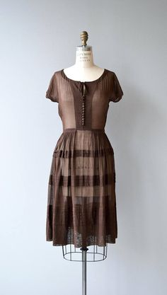 Vintage 1950s semi-sheer chocolate brown cotton voile dress with aesthetic buttons down the front, tie detail at neckline and metal zip closure at the side. --- M E A S U R E M E N T S --- fits like: medium bust: 36-38 waist: 28 hip: free length: 41 brand/maker: n/a condition: excellent to ensure a good fit, please read the sizing guide: http://www.etsy.com/shop/DearGolden/policy ✩ layaway is available for this item ✩ more vintage dresses ✩ http:/&#...