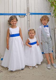 Si votre thème de mariage est le bleu, nous vous proposons des accessoires coordonnés pour un cortège impeccable. Les petits filles portent la robe Louise blanche avec un long tulle et le petit garçon porte l'ensemble gris perle.