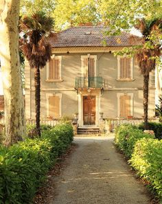 South of France. Beautiful french country home , stucco shutter, peaked and tiled roof, crush pathway entry