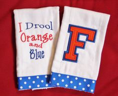 Set of 2 burp cloths. The first one has an applique logo, the other is embroidered with I Drool Orange and Blue. Both are edged in royal blue polka