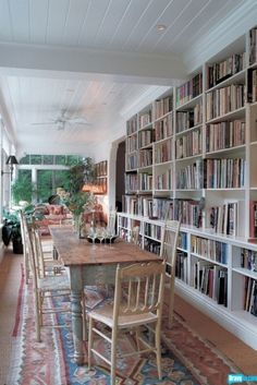bookshelf wall looking onto a brunch table in a screened porch