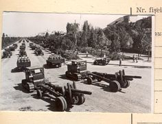 """S-80 """"Stalinets"""" artillery tractors of the Romanian People's Army towing ML-20 152mm howitzer guns rolling past the General Military Academy in Bucharest at the 1950 Romanian Liberation Day Parade."""