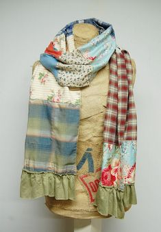 This boho patchwork scarf is constructed of 100% recycled fabric in a beautiful array of colors and designs. The raw edges and exposed stitching lend to the unique tattered design. The ends are trimmed in shabby ruffles. The scarf measures approximately 14 wide and 85 in length. Care: