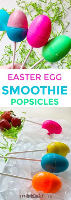 Three Easter plastic easter eggs, one blue pink and green are being held with sticks coming out of the bottom. The blue Easter Egg is open to reveal frozen red smoothie popsicle inside. Behind the Easter egg popsicles, green Easter grass can be seen scattered on the table. At The bottom of the immage is four Easter Egg popsicles sitting on a platter full of ice. To the left of the platter is a pile of three strawberries sitting among some green easter grass.