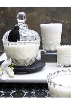 "Made from clean burning soy wax and lead free cotton wick, this curvaceous candle personifies the golden age of hollywood. It's glass scalloped base, lid, and scent dipped tassel will decadently dress your home. We encourage you to re-purpose the vessel to aptly house your trinkets and treasures. Approx. 70 - 80 hours of burn time. 10 oz. wax blend Measures: 6 inches high with lid, 2.75"" base, 4"" diameter   Amber Noir Cabochon Candle by DAVINCI. Home & Gifts - Home Decor - Candles & Scents…"