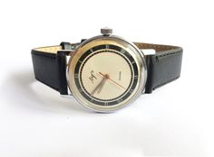 Awesome Silver Soviet vintage watch made in 80s.  Soviet Vintage Watch Mechanical Luch with 23 jewels and awesome white with black dial. Watch in great condition. Works perfect. Mens watch comes with new black leather strap. Made in 80s in USSR.  Vintage mechanical mens watch Luch made by Minsk Watch Factory (Minsk, Belorussia) which was founded in 1953. This Watch Factory is Belorussias oldest factory.  Case in diameter 1,4 inches (3,5 cm)  This is a mechanical watch, so Wind-up it…