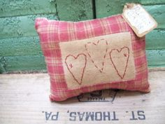 "primitive valentine heart stitchery pillow. $5.00 small tuck bowl filler rustic simple fabric stitched pillow. The pillow has a dark pink homespun border. The pillow has been heavily stained all over for a great primitive look. This little pillow would be great for adding to a Valentine gathering, toss in a bowl or tucked in an old cupboard. Measures 5 1/2"" wide and 4 1/2"" tall."