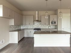 Kitchen in light gray EVRGRN Artisk engineered wood with dark wood floors, warm gray countertops and clear glass pendants