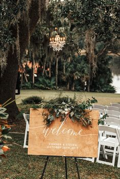 rustic wood welcome sign with white calligraphy for the outdoor wedding ceremony is adorned with eucalyptus and magnolia greenery, ferns, sweet almond tree blooms and white spray roses.