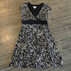 White House Black Market dress Black and white dress with a solid black band under bust. Has a little cap sleeve and a tie in the back. Nice light weight material which creates a perfect flowy dress, perfect for summer. White House Black Market Dresses