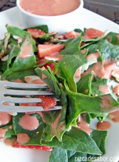 Aprende a preparar un delicioso aderezo de fresa (fácil y listo en menos de 3 minutos) con una ensalada de espinaca, fresas, aguacate y almendras.