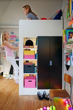 Vista de una cama alta con cajas TJENA de colores en las estanterías. Niña sentada en una cama y otra jugando en una escalera.