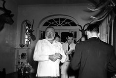 """American novelist Ernest Hemingway meets the press at his Cuban home in San Francisco de Paula, a suburb of Havana, October 28, 1954, after announcement was made that he is awarded the 1954 Nobel Prize in literature. Hemingway said he """"broke the training"""" and took a drink to celebrate the honor."""