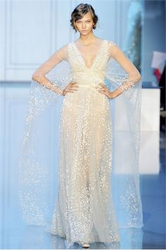 Ivory sheer gown with deep V-neckline and a floating long cape back. Elie Saab designer. Haute Couture Fall Winter 2011/2012 - Vogue.it