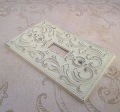 """very pretty vintage metal cast switch plate cover for single toggle / fancy flourish design in repousse style / two tone antique white on gold and lightly distressed -  perfect for your cottage chic / gypsy boho / Paris style decor  Size - 4 3/8"""" x 2.75"""" Weight - 92gms Circa - 1968 Origin - no makers mark Condition - excellent with patina   $14.00 on Etsy"""
