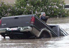cat and owner bail out of sinking pickup truck sinking in Alberta flood waters.