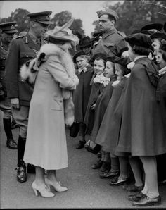 Queen Elizabeth chatting with a group of small girls during a ceremony in  which she presented the Canadian Saskatoon Light Infantry with company  colors, a gift of the people of Saskatoon to their boys serving  overseas. United Kingdom, October 1941.
