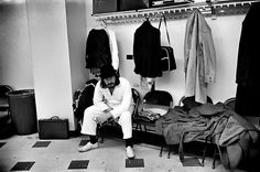 """Led Zeppelin -  Brennan: """"I like this picture. It shows the dreariness of some of these stadiums. Everyone talks about the rock and roll lifestyle but that picture is closer to the reality – seedy back rooms and cloakrooms. John's just killing time, having a cigarette. He was the one I had least contact with; he wasn't very communicative, but he wasn't hostile. In fact, I found Jimmy harder to get on with."""" (Photo: ©Michael Brennan/Proud Galleries)"""