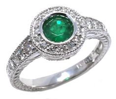 Diamond and emerald ring with 0.30carat total diamond weight and 5mm round emerald in 14k white gold