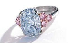 THE MONARCH BLUE DIAMOND: Important Platinum, Rose Gold, Fancy Blue Diamond and Colored Diamond Ring. Centering a carat oval-shaped mixed-cut Fancy Blue diamond, flanked by six round diamonds of pink hue weighing carat. Colored Diamond Rings, Colored Diamonds, Pink Diamonds, Bling Bling, Do It Yourself Fashion, Unusual Rings, Luxury Jewelry, Diamond Jewelry, Fine Jewelry