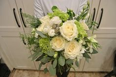 White and green bridal bouquet with hydrangea, roses, ranunculus, lisianthus and eucalyptus. Designed by Forget-Me-Not Flowers.