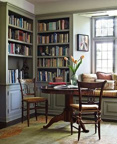 A game table claims a sunlit corner of the library (how I would love to paint the book cases in our music room to lighten it up)