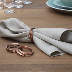 Brushed stainless steel overlaps to wrap napkins in coppery dazzle.