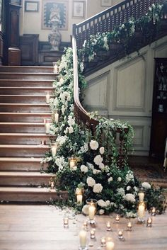 A stunning sweeping staircase with greenery, white roses and candles. rebecca lindon. #roses #weddingdecor #candles