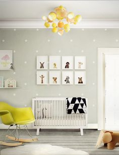Such a cute modern nursery with a yellow & gray theme. Love the polka dot wallpaper, fun, yellow light fixture & animal art wall gallery!