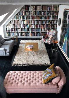 Pink tufted velvet chaise lounge (vintage probably) - Beni Ourain Morrocan rug - Wall to wall bookshelves- Dark wood floors - Small living room / space