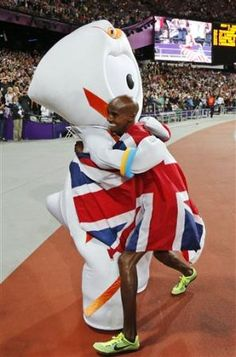 Britain's Mo Farah, right, embraces Wenlock, the games mascot, after winning gold in the men's 10,000-meter during the athletics in the Olympic Stadiu