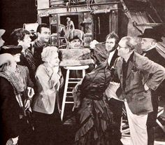 STAGECOACH (1939) - Director John Ford (with hand on hip) & the cast of 'Stagecoach' admire a bronze statue on the set - John Wayne (pictured) - Claire Trevor - Thomas Mitchell (pictured) - John Carradine - Andy Devine (pictured) - George Barcroft (pictured) - Produced by Walter Wanger - Directed by John Ford - United Artists - Publicity Still.