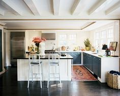 i am a big fan of hardwood floors in kitchens and love a traditional rug over the dark floors.  also love the cabinet fronts are NAVY not black