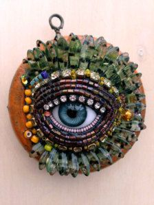 2.75x2.75x1  This unique beaded wall eye by Betsy Youngquist features an antique glass doll eye. This piece started when the artist found two cool old orange shower curtain rings at an antique store. The eye is surrounded by glass beads, glass stones, antique glass seed beads, vintage glass stones, and Czech rhinestones. These surface materials were adhered using a mosaic process. Eyes are a symbol of protection. There is a hole on the back for hanging on the wall.