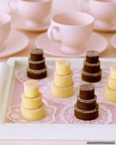 "stead of the traditional wedding cake, treat guests to their own tiered ""cake."" For these fudge treats, which can be made with white or dark chocolate, cookie cutters form bite-size layers resembling those on a wedding cake. Pink sanding sugar serves as icing, and paper doilies enhance the dainty display."