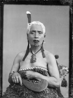 Tattoed Maori woman wearing traditional garb – a cloak made of kiwi feathers.