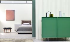 The bedroom is left capacious, with just the bed and stool peeking out in different grey shades, allowing for the alternatively rusted red artwork and grass green sideboard to become the focus