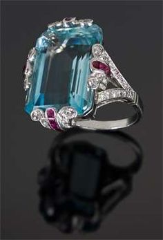 A large aquamarine ring with diamond and ruby set trefoil platinum claws