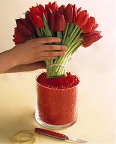 Use baby food jars, red, pink and white candies and put two short flowers in each jar.