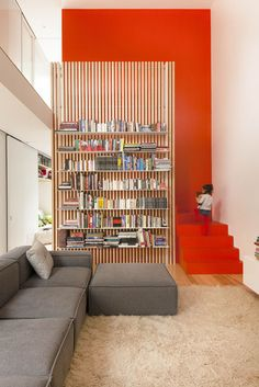 The stairs are partically hidden behind a slatted ash screen that supports steel bookshelves. Photo by Maxime Brouillet.