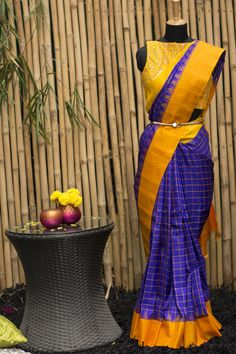 Waistbelt n bluse This stunning pure gadhwal silk saree is in a exotic shade of rich blue checked with fine lines in mustard orange, bordered on dual sides with a shade of yellow and orange with temple motif touches.