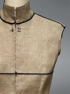 """Maison Margiela (French, founded 1988). Martin Margiela (Belgian, born 1957). Waistcoat(detail), spring/summer 1997, Semi–Couture. Machine–sewn natural linen plain weave, hand–stamped with Stockman dummy text: """"SEMI COUTURE,"""" """"PARIS/BREVETTE S.G.E.G/35059,"""" and """"42,"""" hand–sewn hook–and–eye closures. Photo © Nicholas Alan Cope. #ManusxMachina #CostumeInstitute"""