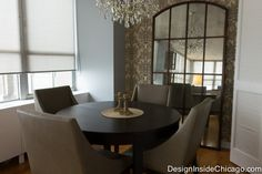 A modern table and chairs offset with an antiqued mirror with dramatic wall covering create an eclectic look in this Chicago living room and dining room space