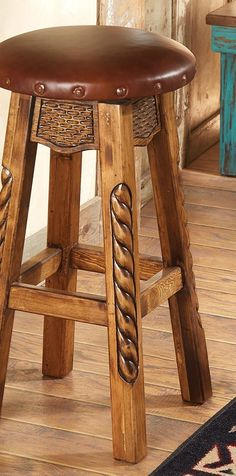 Carved Western Bar Stool: A chip-carved apron and rope-carved legs add rugged detail to this barstool with a brown leather seat and nailhead trim. Available in bar or counter height.