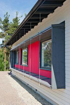 Rauman palvelutalon julkisivun panelointia on piristetty harmaaksi ja punaiseksi maalatuilla levyillä.